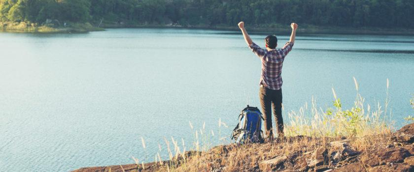 Afbeelding waar een man met zijn handen omhoog staat aan het water