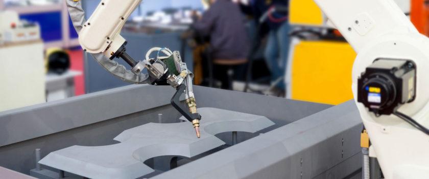 Robot arm die aan het lassen is met op de achtergrond engineers.
